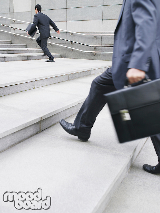 Business men hurrying up steps outdoors side view