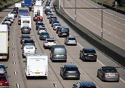 VIDEO AVAILABLE https://we.tl/t-8oDU5ZRYnb © Licensed to London News Pictures. 23/08/2019. Surrey, UK. Traffic builds up clock-wise on the M25 near Cobham in Surrey as people head off for the August Bank Holiday weekend.  Record high temperatures are expected in parts of the United Kingdom over the three day weekend. Photo credit: Peter Macdiarmid/LNP