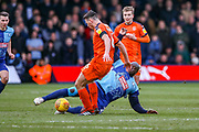 Wycombe Wanderers forward Adebayo Akinfenwa slides in to tackle Luton Town defender Matthew Person during the EFL Sky Bet League 1 match between Luton Town and Wycombe Wanderers at Kenilworth Road, Luton, England on 9 February 2019.