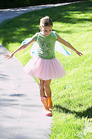 Girl wearing fairy wings and tutu balancing on edge of path portrait