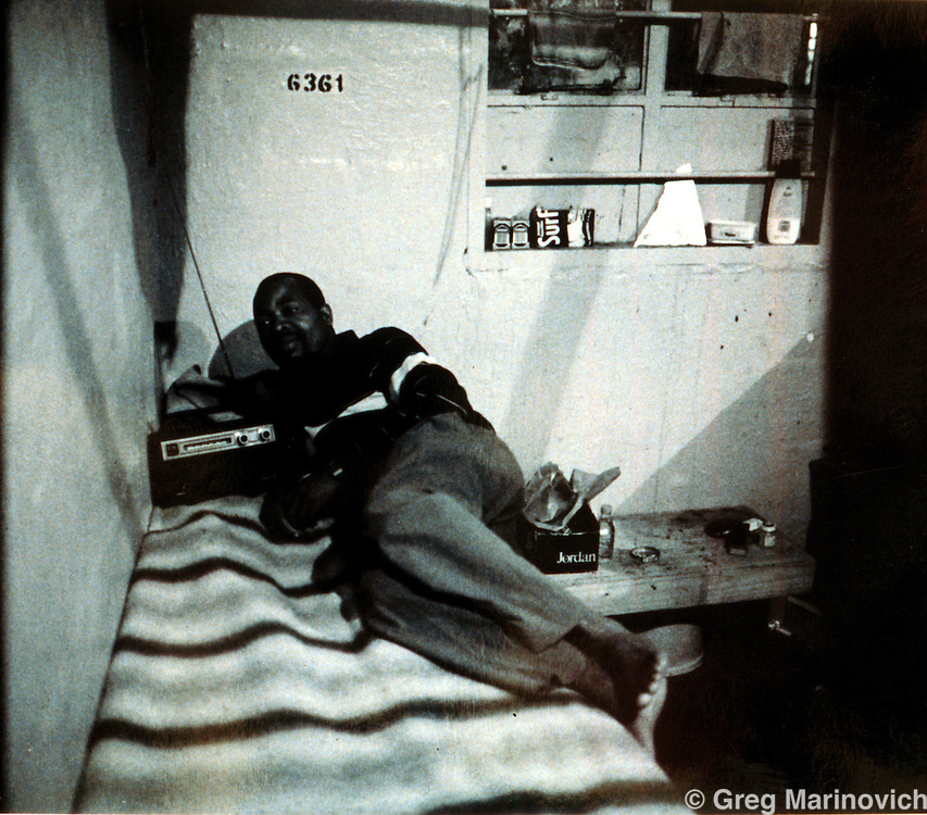 Migrant worker listens to the radio on his bed, number 6361, Mamelodi hostel, Mamelodi, Pretoria, 1989. Scanned from original polaroid. Greg Marinovich