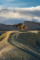 An otherwordly desert landscape in the badlands of Southern Utah as the rolling desert hills lead to the rocky sandstone outcrops at sunset.