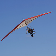 A hang glider with passenger landing at Sao Conrado beach after  flying above the hillside of Pedro Bonita high in the hills of Rio de Janeiro. Pilots of hang gliders and para gliders take tourists for tandem flights with breathtaking views of the city before landing on Sao Conrado beach. Rio de Janeiro,  Brazil. 9th September 2010. Photo Tim Clayton.