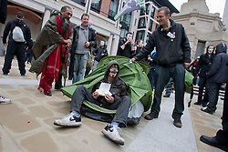 © licensed to London News Pictures. London, UK 01/05/2012. A protester sitting in a tent as Occupy London protesters gathering at Paternoster Square, outside London Stock Exchange, before their march for May Day in London. Photo credit: Tolga Akmen/LNP