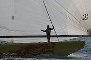 China Team crewman silhouetted by backlit spinnaker gives thumbs up after proudly taking team-best sixth place in America's Cup fleet race, Act 11; Valencia, Spain.