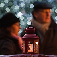 VERONA, ITALY - DECEMBER 04: A candle lit Christmas lantern stands in front of a couple and christmas light at the Verona Christmas Market on December 4, 2010 in Verona, Italy. Christmas markets, fairs, lights and nativity scenes fill Northern Italian cities and villages from December through January 6.