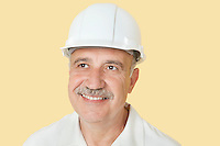Happy senior man with hardhat over yellow background