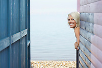 Woman leaning out of beach house verandah portrait
