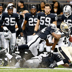 Aug 16, 2013; New Orleans, LA, USA; Oakland Raiders defensive back Shelton Johnson (42) and defensive end Andre Carter (97) tackle New Orleans Saints running back Darren Sproles (43) during the first quarter of a preseason game at the Mercedes-Benz Superdome. Mandatory Credit: Derick E. Hingle-USA TODAY Sports