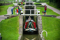 A canal boat exits one of the locks in the lower staircase at Foxton Locks on the Grand Union Canal, Leicestershire, England, UK.