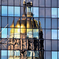 Georgia State Capitol Dome Reflection at Sunset in Atlanta, Georgia<br /> The gold leaf covering the Georgia State Capitol is from Lumpkin County, the site of the first US gold rush that started in 1828. When it was gilded again in 1958, Dahlonega and Lumpkin citizens donated gold from the same era. On top of the dome is a 1,800 pound, 26 foot tall, copper statue. It is informally called Miss Freedom. Her official name is Goddess of Liberty. She carries a sword in one hand and a torch in the other. They both shine brightly in this skyscraper reflection at sunset.