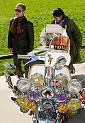 A mod couple standing behind a scooter with many lights and mirrors, London, UK, 2008