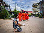 16 JUNE 2016 - PAKSE, CHAMPASAK, LAOS: A woman prays as Buddhist monks walk towards her on their morning Tak Bat, or alms rounds in Pakse. The monks walk through the community just after sunrise accepting alms from people. Pakse is the capital of Champasak province in southern Laos. It sits at the confluence of the Xe Don and Mekong Rivers. It's the gateway city to 4,000 Islands, near the border of Cambodia and the coffee growing highlands of southern Laos.      PHOTO BY JACK KURTZ