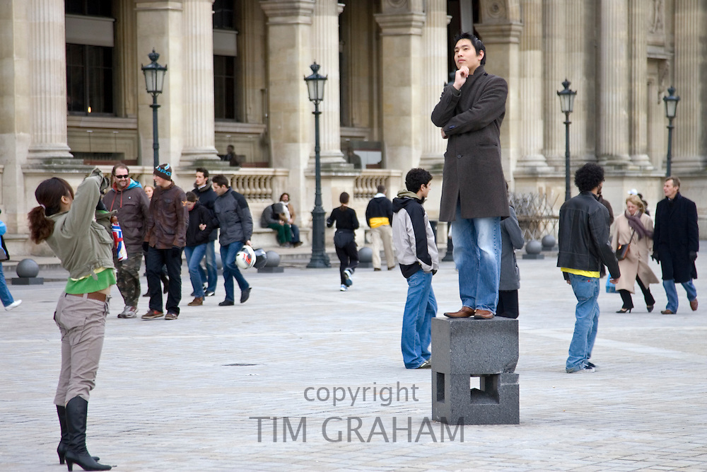 Tourist has his photograph taken balancing on posing plinth outside the Louvre Museum, Paris, France