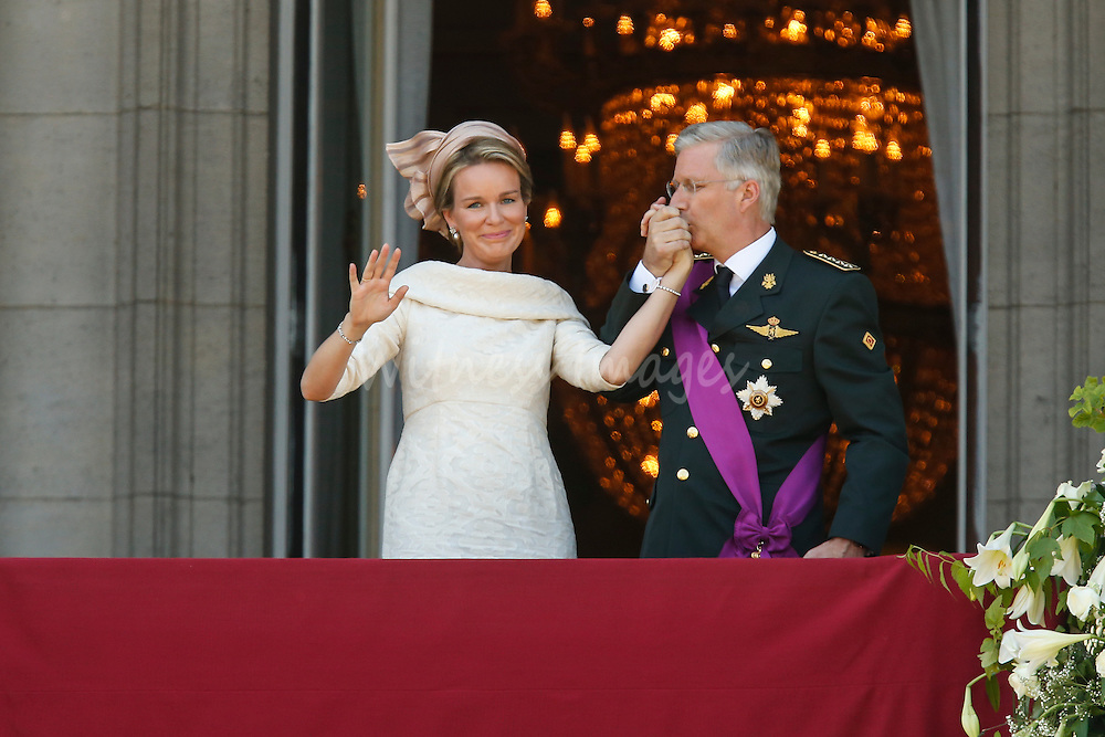 Queen Mathilde of Belgium (L) and King Philippe of Belgium (R) greet the crowd from the balcony of the Royal Palace after his swearing-in ceremony in Brussels on July 21, 2013. Witness Images/Thierry Roge