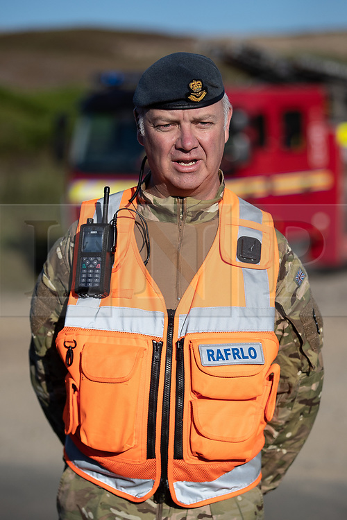 "© Licensed to London News Pictures . 28/06/2018 . Saddleworth , UK . Wing Commander GARY LANE Lane (l), RAF Regional Liaison Officer for the North West at a press conference at Higher Swineshaw Reservoir . The army are being called in to support fire-fighters , who continue to work to contain large wildfires spreading across Saddleworth Moor and affecting people across Manchester and surrounding towns . Very high temperatures , winds and dry peat are hampering efforts to contain the fire , described as "" unprecedented "" by police and reported to be the largest in living memory . Photo credit: Joel Goodman/LNP"