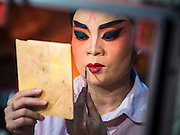 "26 NOVEMBER 2014 - BANGKOK, THAILAND: A performer puts on her makeup before a Chinese opera performance at the Chow Su Kong Shrine in the Talat Noi neighborhood of Bangkok. Chinese opera was once very popular in Thailand, where it is called ""Ngiew."" It is usually performed in the Teochew language. Millions of Chinese emigrated to Thailand (then Siam) in the 18th and 19th centuries and brought their culture with them. Recently the popularity of ngiew has faded as people turn to performances of opera on DVD or movies. There are about 30 Chinese opera troupes left in Bangkok and its environs. They are especially busy during Chinese New Year and Chinese holidays when they travel from Chinese temple to Chinese temple performing on stages they put up in streets near the temple, sometimes sleeping on hammocks they sling under their stage.      PHOTO BY JACK KURTZ"