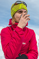 A feamle mountaineer drinks a warm tea on a sunny Winter day in Mont Blanc Massif.