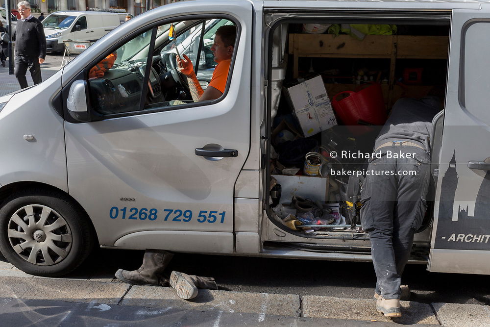 Two workmen parked in their company van, check messages and organise tools in the rear, in the City of London, the capital's financial heart, on 25th September 2018, in London, England.