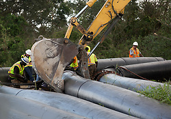 September 13, 2017 - Belle Glade, Florida, U.S. - Workers dismantle bypass pipes at the Herbert Hoover Dike culvert 12A replacement project. Debris from Hurricane Irma was cleaned out of the bypass pipes so that canal water can be  pumped into Lake Okeechobee near Belle Glade, Florida on September 13, 2017. (Credit Image: © Allen Eyestone/The Palm Beach Post via ZUMA Wire)