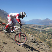 Zach Baker from Waimauku in action during the New Zealand South Island Downhill Cup Mountain Bike series held on The Remarkables face with a stunning backdrop of the Wakatipu Basin. 150 riders took part in the two day event. Queenstown, Otago, New Zealand. 9th January 2012. Photo Tim Clayton