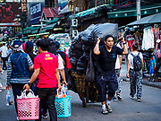 01 AUGUST 2018 - BANGKOK, THAILAND:  A vender hauls his merchandise down Khao San Road in Bangkok before city code enforcement officers ticketed venders in the street market. Khao San Road is Bangkok's original backpacker district and is still a popular hub for travelers, with an active night market and many street food stalls. The Bangkok municipal government went through with it plans to reduce the impact of the street market on August 1 because city officials say the venders, who set up on sidewalks and public streets, pose a threat to public safety and could impede emergency vehicles. Venders are restricted to working from 6PM to midnight and fewer venders will be allowed to set up on the street. It's the latest in a series of night markets and street markets the city has closed.   PHOTO BY JACK KURTZ