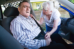 Woman helping husband with Alzheimer's Disease to put on a seat belt in the car,