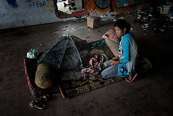 An addict with her newborn child in an abandoned building, Phnom Penh, Cambodia.<br />