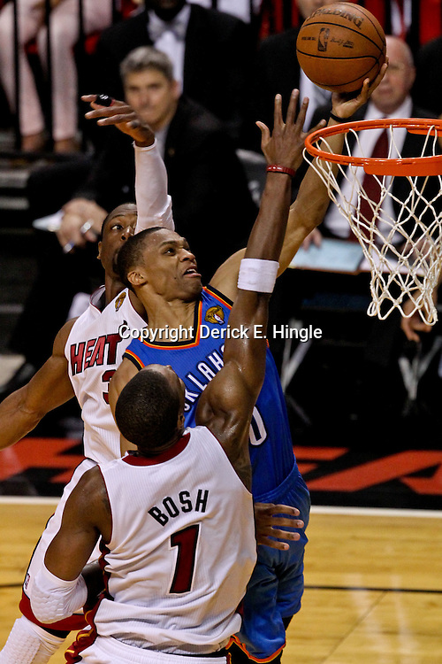 Jun 21, 2012; Miami, FL, USA; Oklahoma City Thunder point guard Russell Westbrook (0) shoots over Miami Heat power forward Chris Bosh (1) and Miami Heat shooting guard Dwyane Wade (3) during the third quarter in game five in the 2012 NBA Finals at the American Airlines Arena. Mandatory Credit: Derick E. Hingle-USA TODAY SPORTS