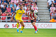 Lynden Gooch (#11) of Sunderland AFC heads clear of Nesta Guinness-Walker (#18) of AFC Wimbledon during the EFL Sky Bet League 1 match between Sunderland and AFC Wimbledon at the Stadium Of Light, Sunderland, England on 24 August 2019.