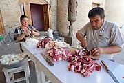 Uzbekistan, Khiva, Dekhon Bazaar.<br /> Cutting meat and onions to fill Somsa (dumplings baked in a tandyr oven).