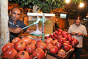 Israel, Acre, Man squeezes fresh pomegranate juice at a stall in the market
