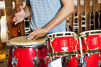Midsection of a man playing bongo drums in music store