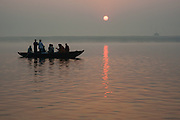 Tourists on boat on the Ganges river at Varanasi at dawn (India)