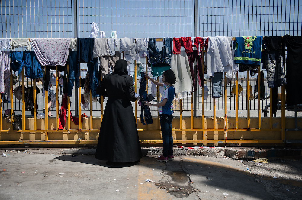 A Syrian mother and her daughter are hanging clothes at the port railings of Mytiline. Very often the overcrowded dinghies that carry them from Turkey fill with water and all their belongings becoming wet.