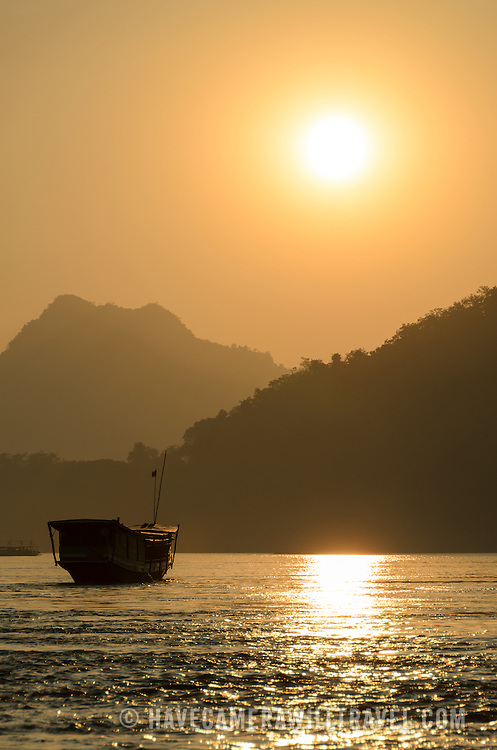 A covered wooden boat is silhouetted against the sunset on the Mekong River near Luang Prabang, Laos.