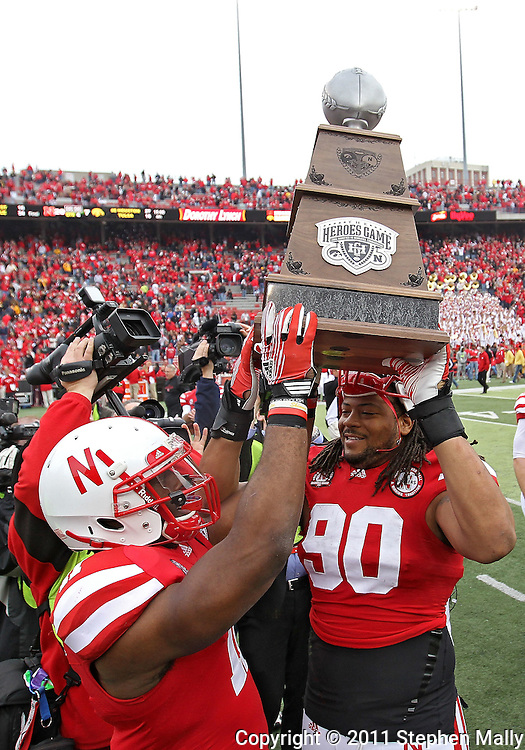 November 25, 2011: Nebraska Cornhuskers running back Curenski Gilleylen (11) and Nebraska Cornhuskers defensive tackle Terrence Moore (90) hold up the Heroes Game Trophy after the end of the NCAA football game between the Iowa Hawkeyes and the Nebraska Cornhuskers at Memorial Stadium in Lincoln, Nebraska on Friday, November 25, 2011. Nebraska defeated Iowa 20-7.