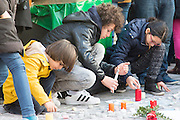 Brussels 23 March 2016. People from Brussels gathered at the Beurs square in the center of town to remember the victims of the terrorist attacks at Zaventem and Maalbeek underground station.Children lighting candles