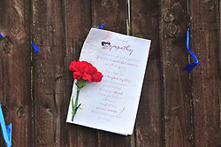 © Licensed to London News Pictures.10/04/2018<br /> HITHER GREEN, UK.<br /> A SINGLE ROSE AND CARD ARE LEFT HANGING THIS AFTERNOON ABOVE A PILE OF FLOWERS ON THE PAVEMENT AFTER BEING CUT DOWN AGAIN.<br />  Hither Green Burglary Murder. South Park Crescent,Hither Green.<br />  Flowers outside the home of 78 year old Richard Osborn-Brooks who stabbed a burglar to death in his home.<br /> Photo credit: Grant Falvey/LNP