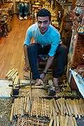 Man carving wood with his toes