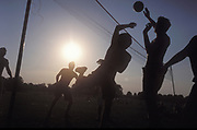 A silhouette of people playing volleyball in the park, UK 2004