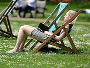© Licensed to London News Pictures. 22/05/2012. London, UK A woman relaxes whilst sitting on a deck chair in the sun in Hyde Park.  People enjoy the sunshine in London's Royal Parks today 22 May 2012. Photo credit : Stephen Simpson/LNP