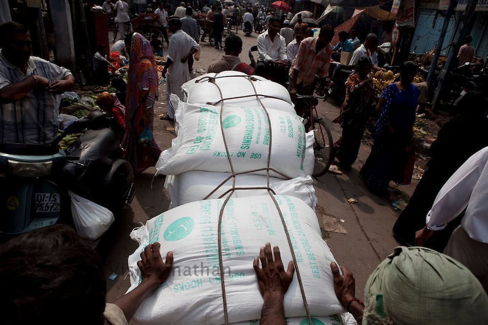 Labourers push a hand cart carrying one quintal of sugar through the busy wholesale market of Old Delhi, in New Delhi, India, on Wednesday September 2, 2010. Photographer: Prashanth Vishwanathan/Bloomberg News