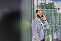 Portrait of young attractive businessman talking on smartphone