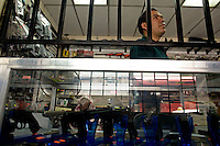 A employee of a gun shop stands behind a protective gate in Guatemala City May 19, 2009. In recent days the country of Guatemala is dealing with unrest as the Presidnet Alvaro Colom and Guatemala's business elite are embroiled in a scandal involving money laundering, embezzling government funds and ordering assassinations, following the murder of a prominent lawyer Rodrigo Rosenberg. (Darren Hauck)