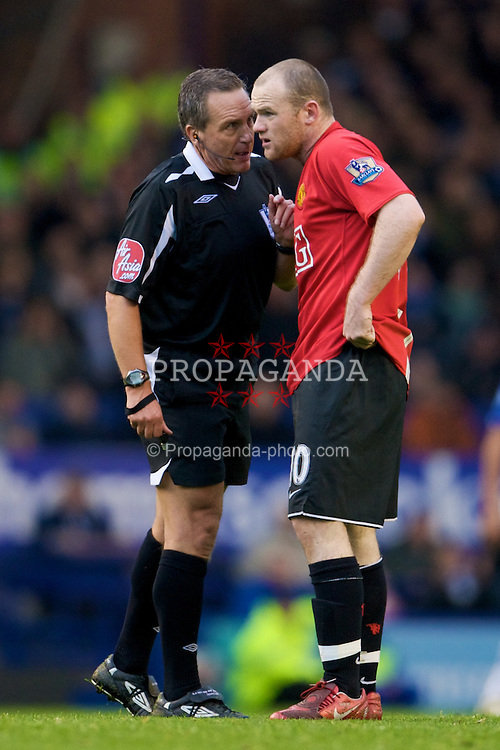 LIVERPOOL, ENGLAND - Saturday, October 25, 2008: Manchester United's Wayne Rooney is spoken to by referee Alan Wiley after antagonises the Everton supporters seconds after being booked for a reckless, late and high challenge during the Premiership match at Goodison Park. (Photo by David Rawcliffe/Propaganda)