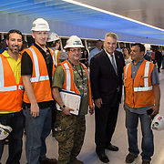 New York Congressman Peter King poses with construction workers at opening of Moynihan Train Hall in Penn Station.