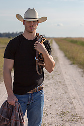 handsome rugged cowboy standing on a dirt road with reins over his shoulder