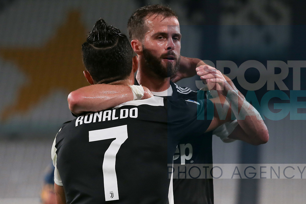 Juventus's Portuguese striker Cristiano Ronaldo is embraced by team mate and Bosnian midfielder Miralem Pjanic after scoring from the penalty mark to give the side a 2-0 lead during the Serie A match at Allianz Stadium, Turin. Picture date: 26th June 2020. Picture credit should read: Jonathan Moscrop/Sportimage