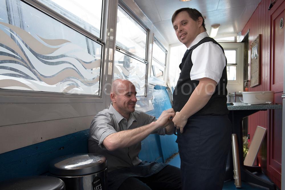 Nicola, restaurant manager, helping David to wear the uniform waiter